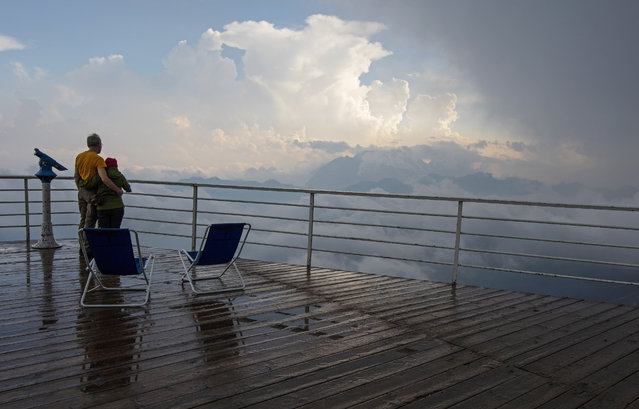 Visitors watch from the Rifugio Lagazuoi as a thunderstorm approaches in the Dolomite Mountains near Cortina d' Ampezzo in northern Italy July 16, 2015. (Photo by Bob Strong/Reuters)