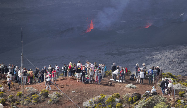 "Volcano-watchers gather on an overlooking vantage point as lava erupts from the Piton de la Fournaise ""Peak of the Furnace"" volcano, on the southeastern corner of the Indian Ocean island of Reunion Saturday, August 1, 2015. (Photo by Ben Curtis/AP Photo)"