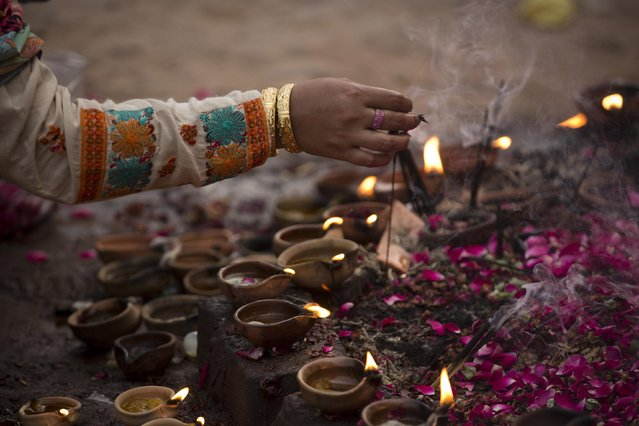 A Pakistani Muslim devotee lights oil clay lamps at a local shrine in suburbs of Islamabad, Pakistan, Thursday, July 23, 2015. (Photo by B. K. Bangash/AP Photo)