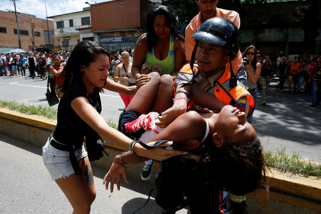 A police officer carries a woman who fainted while gathering to try to buy pasta outside a supermarket in Caracas, Venezuela, June 10, 2016. (Photo by Carlos Garcia Rawlins/Reuters)