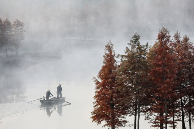 People ride a boat on the Tianquan Lake during a foggy day in Xuyi in China's eastern Jiangsu province on November 20, 2019. (Photo by AFP Photo/China Stringer Network)