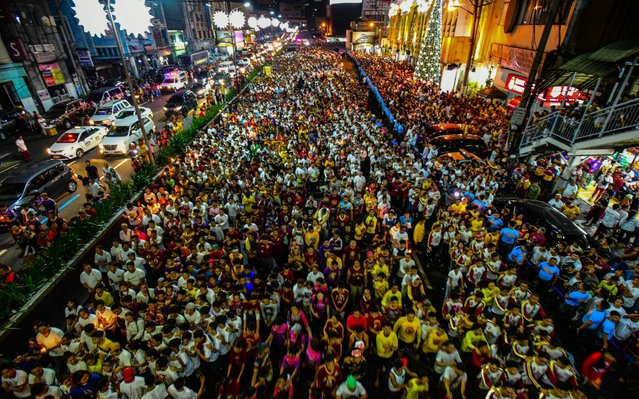 Thousands of devotees participate in an annual Thanksgiving procession with the image of the Black Nazarene in Manila on December 31, 2019. Thousands of barefoot devotees will join the religious procession in Manila, starting New Year's Eve and ending each January 9, hoping to touch a centuries-old icon of Jesus Christ, called the Black Nazarene, which is believed to have miraculous powers. (Photo by Maria Tan/AFP Photo)