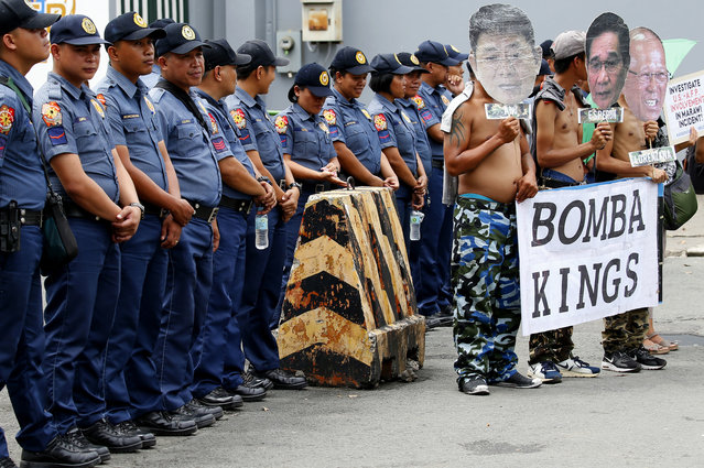 Protesters display portraits of (from left) Armed Forces chief Gen. Eduardo Ano, National Security Adviser Hermogenes Esperon Jr., and Defense Chief Delfin Lorenzana, during a rally outside Camp Aguinaldo, the general headquarters of the Armed Forces of the Philippines, to protest the extension of Martial Law in the whole of Mindanao island in southern Philippines as proposed by President Rodrigo Duterte Thursday, July 20, 2017, in Quezon city northeast of Manila, Philippines. Martial Law was declared by Duterte last May 23 for 60 days following the siege by Muslim militants of Marawi city which continues for almost two months now. (Photo by Bullit Marquez/AP Photo)