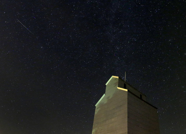 In this photo taken with long exposure, a meteor streaks across the sky behind a grain elevator during the annual Perseid meteor shower Thursday, August 13, 2015, in Baxter, Iowa. (Photo by Charlie Riedel/AP Photo)