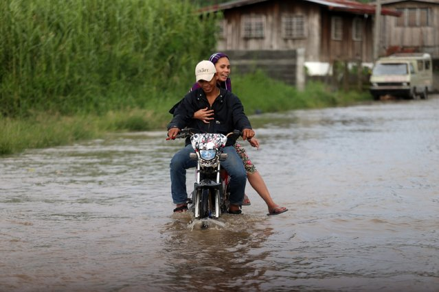 A motorcyclist crosses a flooded road on July 15, 2014 in Sultan Kudarat, Mindanao, Philippines. Thousands of people have been fleeing coastal areas of Philippines as the first major typhoon of the season is expected to make landfall this evening. Typhoon Rammasun is heading towards eastern Philippines and is likely to pass over the capital city Manila on its way through the country. (Photo by Jeoffrey Maitem/Getty Images)