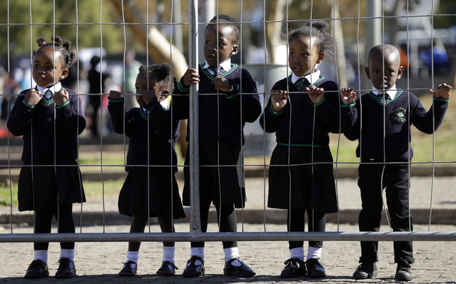 Children wearing school uniforms watch the laying of wreaths, at the Hector Pieterson Memorial in Soweto, South Africa, Thursday, June 16, 2016, for commemoration of the 40th anniversary of uprisings. South Africans are commemorating the 40th anniversary of a pivotal moment in the anti-apartheid struggle, a 1976 black student uprising in the Soweto area of Johannesburg that led to a deadly crackdown but launched a new phase of opposition to white minority rule. (Photo by Themba Hadebe/AP Photo)