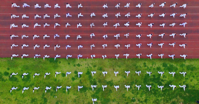 This photo taken using a drone shows people performing Tai Chi as part of a National Fitness Day event in Rongan in China's southwestern Guizhou province on August 8, 2017. National Fitness Day has been held on August 8 every year since 2009 to mark the anniversary of the opening of the 2008 Beijing Olympic Games. (Photo by AFP Photo/Stringer)