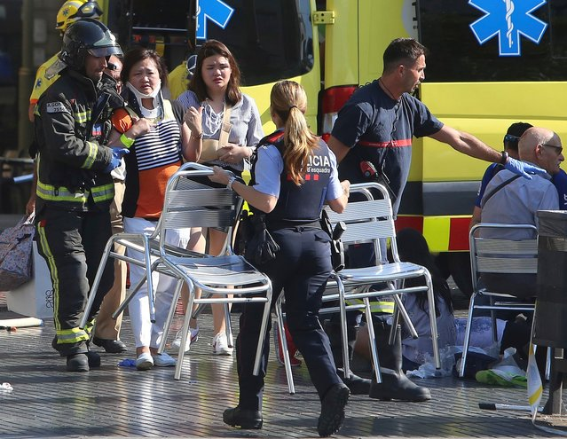 Injured people are treated in Barcelona, Spain, Thursday, August 17, 2017 after a white van jumped the sidewalk in the historic Las Ramblas district, crashing into a summer crowd of residents and tourists and injuring several people, police said. (Photo by Oriol Duran/AP Photo)