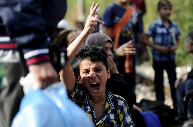 A boy gestures to the police at the border line dividing Macedonia and Greece August 21, 2015. (Photo by Ognen Teofilovski/Reuters)