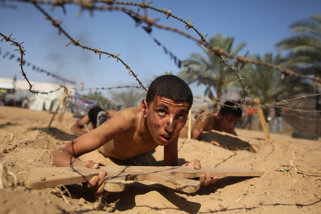 A Palestinian boy takes part in a military-style summer camp being held by the Islamic Jihad movement during the youngsters' summer school vacation in Khan Younes town, in the southern Gaza Strip, 13 July 2016. Thousands of youngsters between the age of six and 16 can participate in the summer camp where they receive military as well as religious training. (Photo by Hatem Omar/EPA)