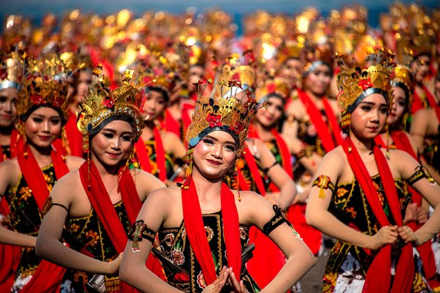 Dancers performed the Gandrung dance during the Gandrung Sewu Festival on the coast of Banyuwangi, East Java, Indonesia, on October 12, 2019. The dance performed by 1350 people became one of the tourist attractions to Indonesia. (Photo by Juni Kriswanto/SURYANTO/Anadolu Agency via Getty Images)