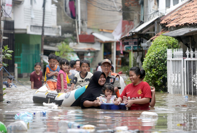 Residents walk in a flooded street in Jakarta, Indonesia, 25 February 2020. According the National Disaster Management Authority (BNPB), heavy rains triggered widespread flooding in Jakarta, with floodwaters reaching a depth of more than 150cm in some areas. (Photo by Adi Weda/EPA/EFE)