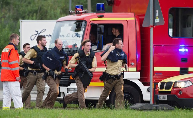 Police officers rush to the scene at a shopping centre in which a shooting was reported, Munich, Germany, 22 July 2016. Several people were reported dead by the police and several more injured after a shooting in the Olympia shopping centre in Munich. (Photo by Matthias Balk/EPA)