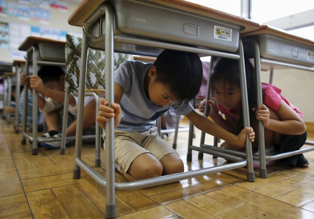 School children take shelter under desks during an earthquake simulation exercise at an elementary school in Tokyo September 1, 2015. (Photo by Toru Hanai/Reuters)