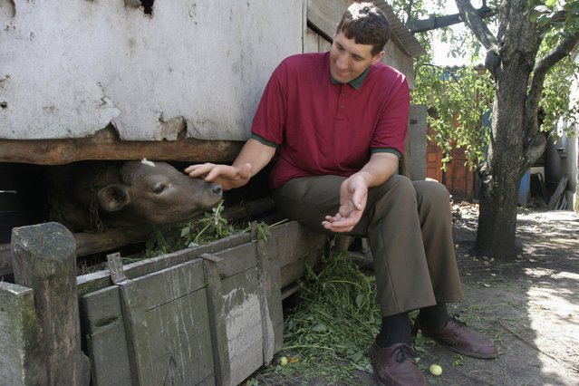 Leonid Stadnyk sits by his house in the village of Podolyantsi in central Ukraine August 11, 2007. Being named the world's tallest man has meant very little for Stadnyk, scraping together a living with his mother in a tiny village. Guinness World Records gave the accolade to him last week. But Stadnyk is prouder of the present from local authorities on his 37th birthday – a bathroom with a shower tall enough to fit his 2.53-metre (8-foot, four-inch) frame. (Photo by Vladimir Sindeyev/Reuters)