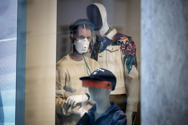 A fashion shop employee, wearing face mask, transparent face shield and medical protective gloves to protect from coronavirus, prepares to put on a mannequin standing in a showcase in Moscow, Russia, Tuesday, April 14, 2020. Russian President Vladimir Putin has ordered most Russians to stay off work until the end of April as part of a partial economic shutdown to stymie the spread of the coronavirus. (Photo by Alexander Zemlianichenko/AP Photo)