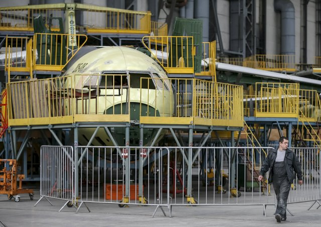 A worker passes a new Antonov airplane at the Antonov aircraft plant in Kiev, Ukraine, September 7, 2015. State-run aircraft maker Antonov built more than 22,000 units of more than one hundred types and modifications of passenger, transport and special-purpose aircraft, including the world's biggest cargo plane Antonov-225 (Mriya), according to the company's official website. (Photo by Gleb Garanich/Reuters)