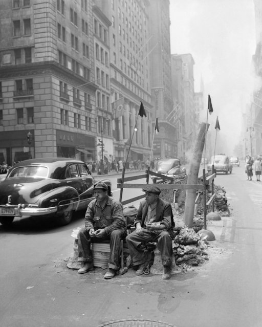 Two workmen eat their lunch beside their excavation on fashionable Fifth Avenue between 56th and 57th Streets in New York, June 8, 1948. (Photo by /Bob Kradin/AP Phot)