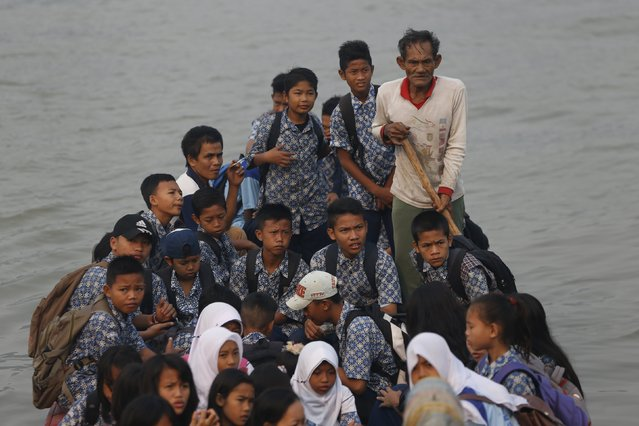 Students sit on a wooden boat as they head home earlier from school, due to the unhealthy quality of air in Palembang, on Indonesia's Sumatra island, September 10, 2015. (Photo by Reuters/Beawiharta)