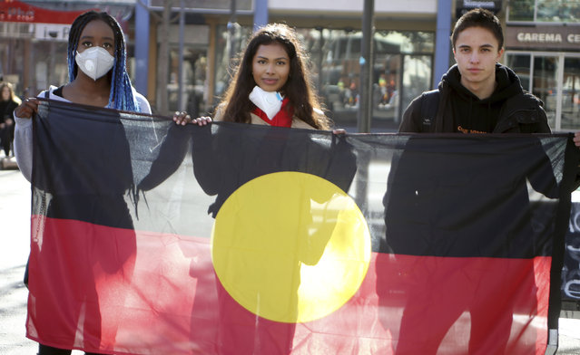 School friends Oluwatobi Odusote, left, Jan Usha and Rhyse Morgan, right, hold an Aboriginal flag in Canberra, Australia, on Friday, June 5, 2020. Thousands gathered in Australia's capital on Friday to remind citizens that the racial inequality underscored by George Floyd's death was not unique to the United States. (Photo by Rod McGuirk/AP Photo)
