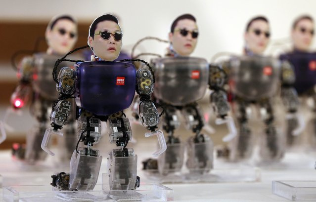 "Robots carrying the face of South Korean rapper Psy dance during a ceremony to promote South Korea's robot industry in Seoul on October 17, 2012. The 34-year-old Psy has rocketed to international fame with his song ""Gangnam Style"" and its much-imitated dance moves which has gone viral on YouTube. (Photo by Yonhap, Park Dong-joo/AP Photo)"