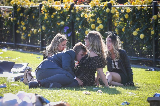A young man nuzzles the breasts of a female companion as they sit on the grass on 2017 Derby Day at Flemington Racecourse on November 4, 2017 in Melbourne, Australia. (Photo by Splash News and Pictures)