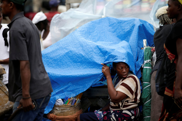 A street vendor covers her stand with a tarpaulin to protect from light rain in a street of Port-au-Prince, Haiti, August 1, 2016. (Photo by Andres Martinez Casares/Reuters)