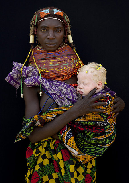 """Albino baby girl and her Mwila mother – Angola. This mwila tribewoman was in Hale and came to me, showing a blue cap coming out from her clothes. i first did not understood there was a baby under this cap. Then she opened her clothes to let appear this albino baby girl. She had some little dreadlocks and was incredibly white. The mother was proud to pause for the picture and discovered the magic of polaroid! I have seen many albinos people in Angola, in the tribes. They are mainly in very bad health, as the sun is very hot there... Perhaps the most moving picture i ever took as the future of this albino baby is not the happiest you can get in this remote area of Africa"". (Eric Lafforgue)"