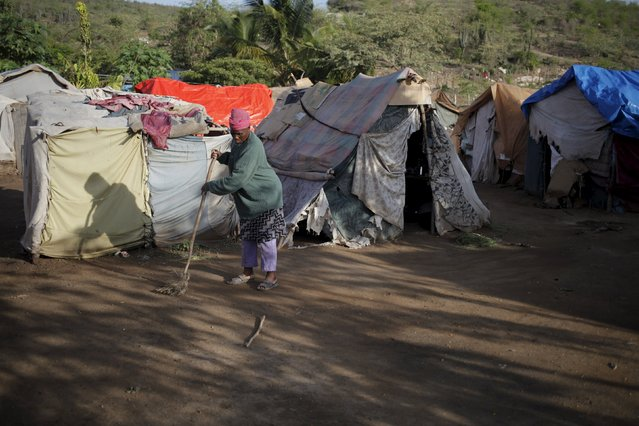 A woman sweeps the ground outside makeshift tents at a refugee camp for Haitians returning from the Dominican Republic on the outskirts of Anse-a-Pitres, Haiti, September 7, 2015. (Photo by Andres Martinez Casares/Reuters)