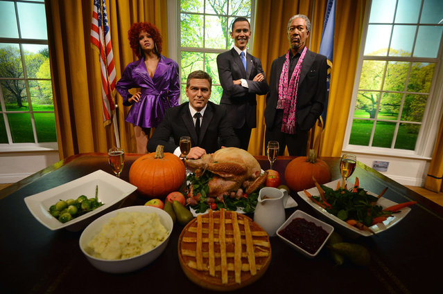 Wax figures of US musician Rihanna (L), actors George Clooney (2nd L) and Morgan Freeman (R) join US President Barack Obama (2nd R) in a recreation of the Oval Office for Thanksgiving at Madame Tussauds in London on November 21, 2012. (Photo by Ben Stansall)