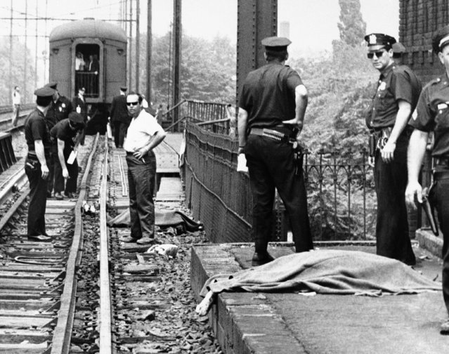 Blankets cover the bodies of a woman (right) and a man (left background) hit by a northbound Penn Central train (background) as they waited with a crowd at Pennsylvania Railroad station in Elizabeth, N.J. on June 8, 1968 to view the southbound train carrying the body of Sen. Robert F. Kennedy to Washington. The woman was identified as Mrs. Antoinette Severini, 54, and the man, John Curia (age unavailable), both of Elizabeth. (Photo by AP Photo)