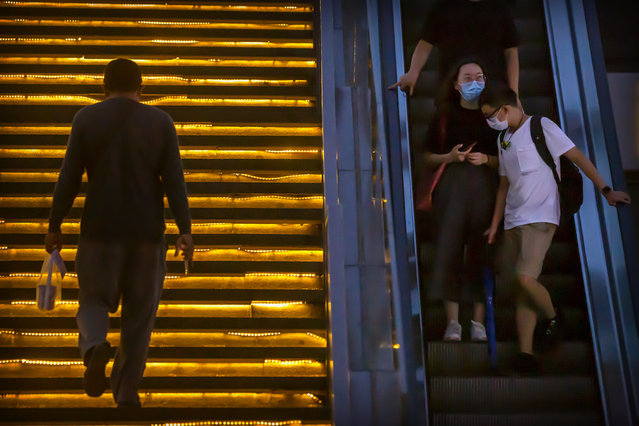 People wearing face masks to protect against the coronavirus ride an escalator at a shopping and office complex in Beijing, Thursday, July 16, 2020. China's economy has rebounded from a painful contraction to grow by 3.2% in the latest quarter compared to a year ago. The expansion came as anti-virus lockdowns were lifted and factories and stores reopened. (Photo by Mark Schiefelbein/AP Photo)