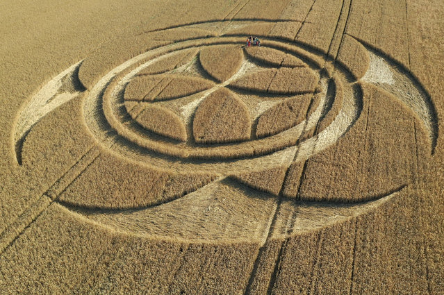 Visitors stand inside a crop circle in a wheat field, which was discovered by a local farmer on July 6 according to local media, close to the Canadian National Vimy Memorial in Vimy, France on July 11, 2020. (Photo by Pascal Rossignol/Reuters)