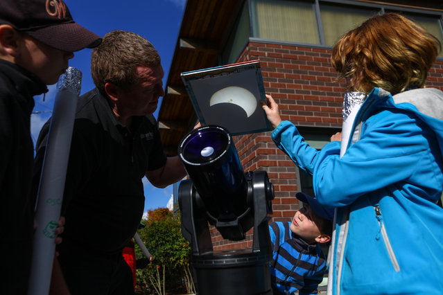 Andrew McCarty and his daughter Zoe McCarty, 11, right, look at a projected image of the sun during a solar eclipse viewing party at the High Point Branch of the Seattle Public Library on Thursday, October 23, 2014. (Photo by Joshua Trujillo/AP Photo/Seattlepi.com)
