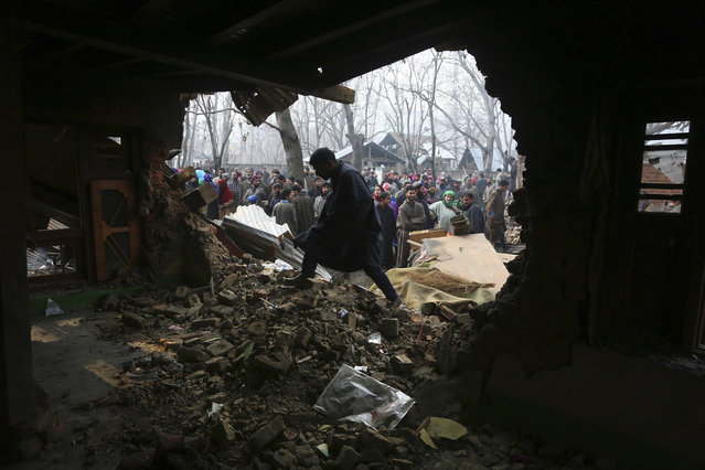 A Kashmiri villager walks across the house which was damaged during a gun-battle at Shopian 55 kilometres (34 miles) south of Srinagar, Indian controlled Kashmir Tuesday, December 19, 2017. Police say a woman was killed during anti-India protests in disputed Kashmir following a gun battle that killed two rebels. Fighting erupted after Indian troops cordoned off a village in the southern Shopian area overnight on a tip that militants were hiding in a house. (Photo by Mukhtar Khan/AP Photo)