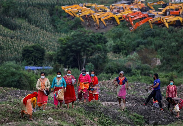 Residents of Khokana and Bungamati work on their fields as part of a protest against the acquisition of their land for a road project, which they say will displace their traditional settlement, and to express their dissatisfaction with the government for not providing them with adequate compensation, in Lalitpur, Nepal on July 18, 2020. (Photo by Navesh Chitrakar/Reuters)