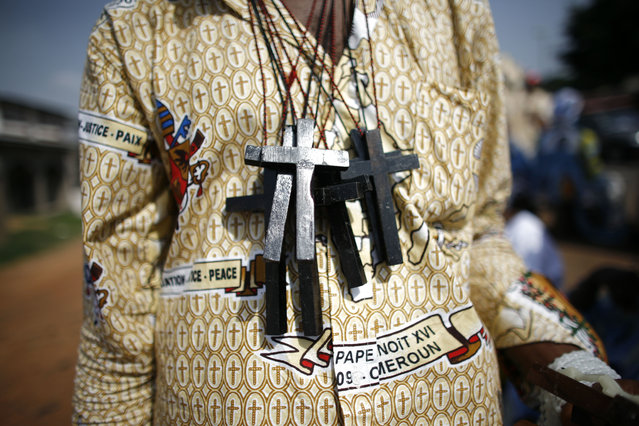 A vendor wears his stock around his neck as he markets crosses to the faithful waiting to see the convoy of Pope Benedict XVI pass, in Yaounde, Cameroon Wednesday, March 18, 2009. (Photo by Rebecca Blackwell/AP Photo)