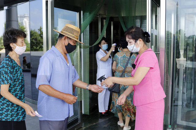 Two employees of the Ryugyong Health Complex disinfect the hands and check the fever of people coming to the complex to help curb the spread of the coronavirus, in Pyongyang, North Korea, Friday, July 31, 2020. (Photo by Jon Chol Jin/AP Photo)