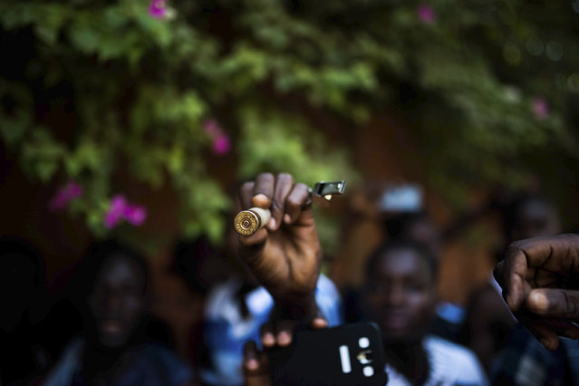 In this photo taken Thursday, October 30, 2014, a protester hold up a bullet as they go on a rampage near the parliament building in Burkina Faso as people protest against their longtime President Blaise Compaore who seeks another term, in Ouagadougou, Burkina Faso. (Photo by Theo Renaut/AP Photo)