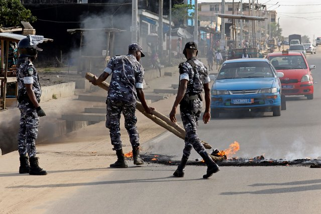 Policemen remove a barricade set on fire by demonstrators to block a road during a protest against president Alassane Ouattara's decision to stand for a third term, in Abidjan, Ivory Coast, August 13, 2020. (Photo by Luc Gnago/Reuters)