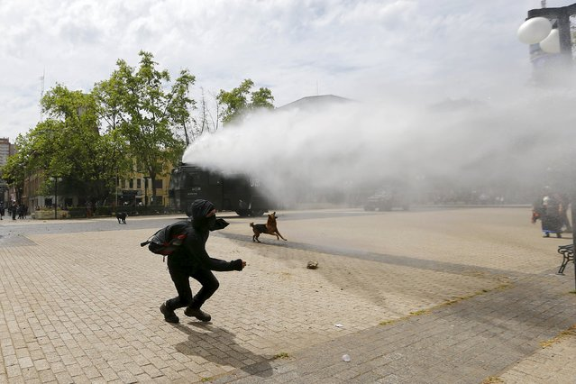 A Mapuche Indian activist runs away from a jet of water released from a riot police vehicle during a protest march by Mapuche Indian activists against Columbus Day in downtown Santiago, Chile, October 12, 2015. (Photo by Ivan Alvarado/Reuters)