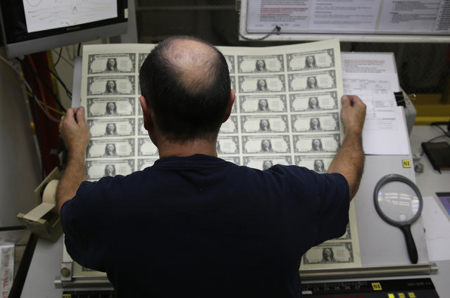 One dollar bills are inspected during production at the Bureau of Engraving and Printing in Washington November 14, 2014. (Photo by Gary Cameron/Reuters)