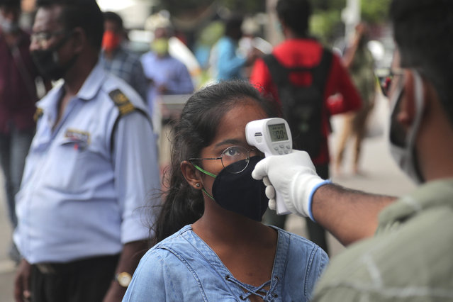 An official checks the body temperature of a candidate wearing a face mask as a precaution against coronavirus before appearing for National Eligibility cum Entrance Test ( NEET) at an exam centre in Hyderabad, India, Sunday, September 13, 2020. NEET is for students who wish to study undergraduate medical and dental courses in government or private medical colleges in India. India's coronavirus cases are now the second-highest in the world and only behind the United States. (Photo by Mahesh Kumar A./AP Photo)