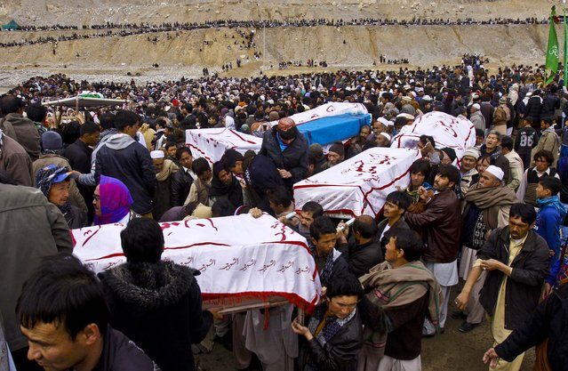 "Shiite Muslims carry the bodies of bombing victims covered with sheets reading, ""we are ready Hussain"", for burial in Quetta, Pakistan, on February 20, 2013. Families buried loved ones who were kin killed during a bombing last weekend. (Photo by Arshad Butt/Associated Press)"
