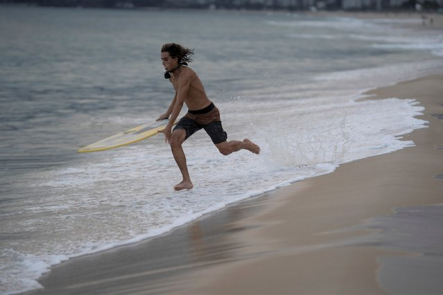 Leo Freitas runs to take a wave at Ipanema beach in Rio de Janeiro, Brazil, Monday, June 8, 2020. For the 18-year-old skimboard athlete, people need to take appropriate precautions when they go out, amid the new coronavirus pandemic, after the authorities have started to reopen gradually some businesses and easing some protective measures. (Photo by Leo Correa/AP Photo)