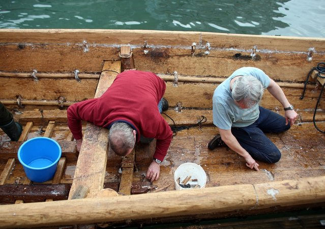 Crew in Britain's first ever full-size reconstructed sea-going Bronze Age boat, bail out water as they prepare to paddle out to sea near to the National Maritime Museum as it makes its maiden voyage on March 6, 2013 in Falmouth, England. (Photo by Matt Cardy)