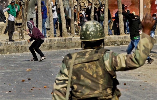 Protesters throw stones at Indian paramilitary soldiers during a protest in Srinagar, India, on March 4, 2013. Most businesses and schools were closed in Kashmir, after separatists called for a strike to demand the return of the body of Mohammed Afzal Guru, who was secretly executed and buried in the Indian capital. (Photo by Mukhtar Khan/Associated Press)
