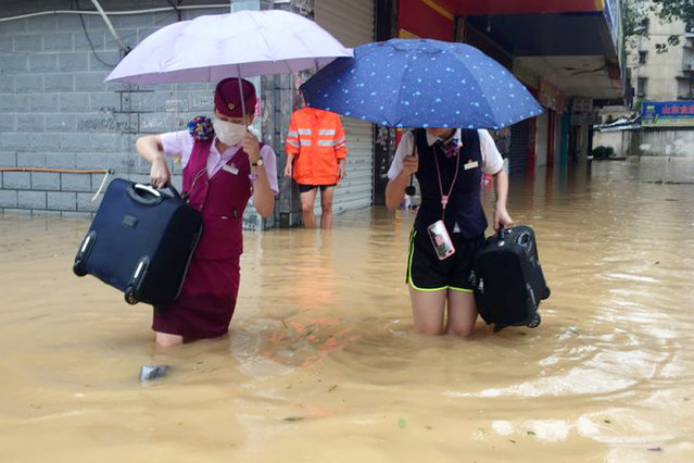 Train attendants carry their luggage as they walk through a flooded street in Fuzhou in southeastern China's Fujian Province Wednesday, September 28, 2016. (Photo by Chinatopix via AP Photo)