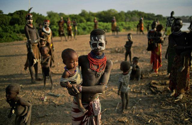 """Members of the Karo tribe pose in front of the Omo river in Ethiopia's southern Omo Valley region on September 23, 2016. The Karo are a Nilotic ethnic group in Ethiopia famous for their body painting. They are also one of the smallest tribes in the region. The construction of the Gibe III dam, the third largest hydroelectric plant in Africa, and large areas of very """"thirsty"""" cotton and sugar plantations and factories along the Omo river are impacting heavily on the lives of tribes living in the Omo Valley who depend on the river for their survival and way of life. Human rights groups fear for the future of the tribes if they are forced to scatter, give up traditional ways through loss of land or ability to keep cattle as globalisation and development increases. (Photo by Carl De Souza/AFP Photo)"""