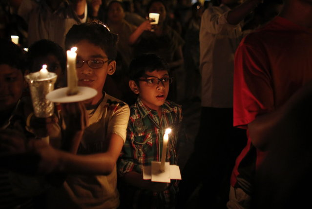 Children hold candles while participating in a candlelight vigil to mark Earth Hour in Mumbai March 23, 2013. Earth Hour, when everyone around the world is asked to turn off lights for an hour from 8.30 p.m. local time, is meant as a show of support for tougher actions to confront climate change. (Photo by Danish Siddiqui/Reuters)
